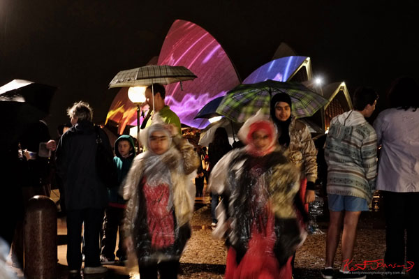People and umbrellas, splash of colour - Sydney Opera House sails in the background - Vivid 2013.
