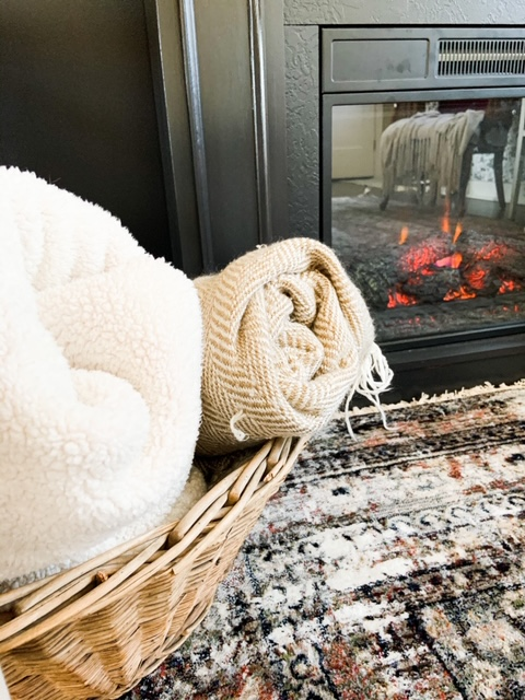 basket of blankets by fireplace