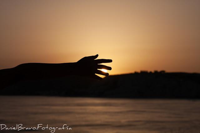 Fotografía de un atardecer en la costa de Sicilia con el brazo de una persona intentando coger el Sol
