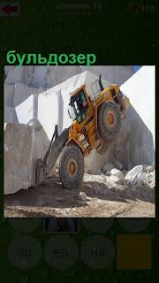 буьдозер задними колесами поднялся на верх, пытаясь поднять тяжелый камень