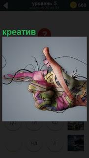 Человеческая ладонь разукрашена креативно узорами и ленточками