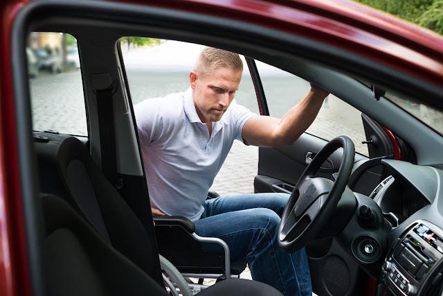 A man in a wheelchair getting into a car