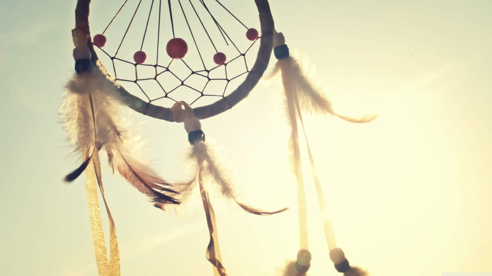 Beautiful closeup photography of a dream catcher against a sky background. With pretty feathers and bead work.