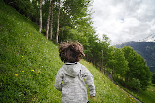 view from behind of a small child running on a grassy hillside