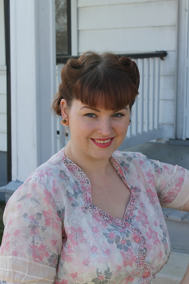 victory rolls with bangs and 1940's sweetheart neckline pink sheer dress