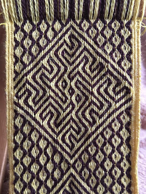 A photo of a tablet woven band with the motif woven in yellow and purple with intersecting diagonal lines