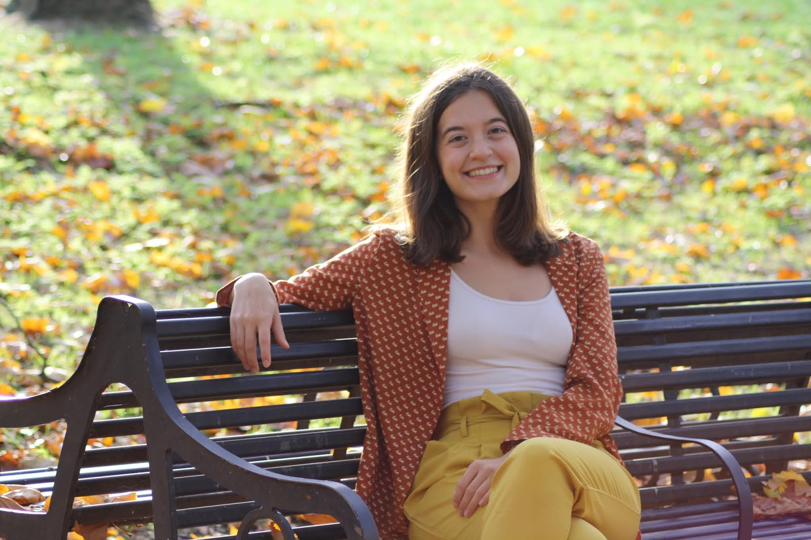 Abbey sits on a park bench wearing a blazer and trousers in autumnal colours, smiling at the camera