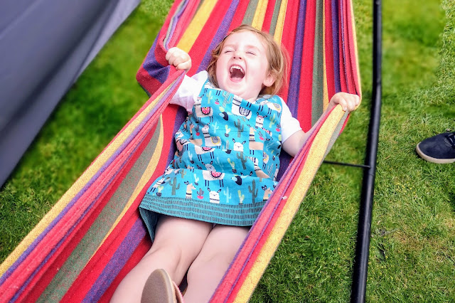 Young girl laughing and enjoying swinging in a free standing rainbow hammock