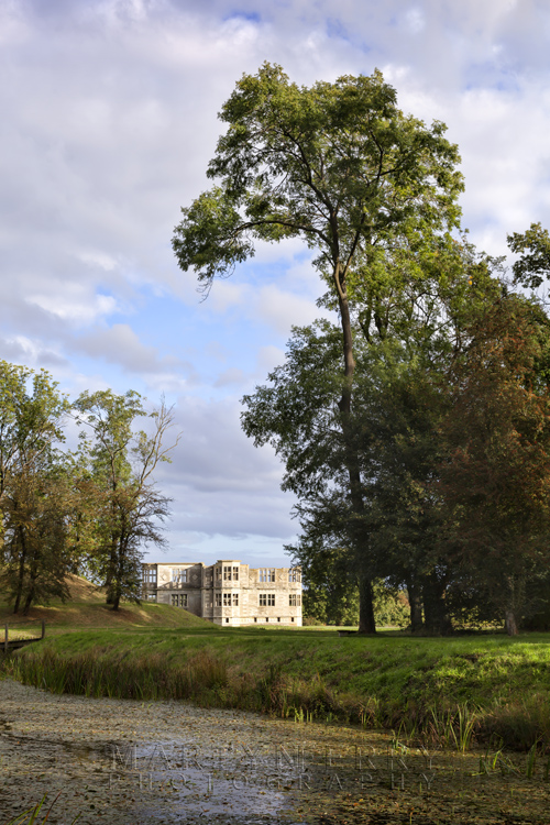 Trees tower over the medieval hall of Lyveden New Bield with ancient moat in the foreground