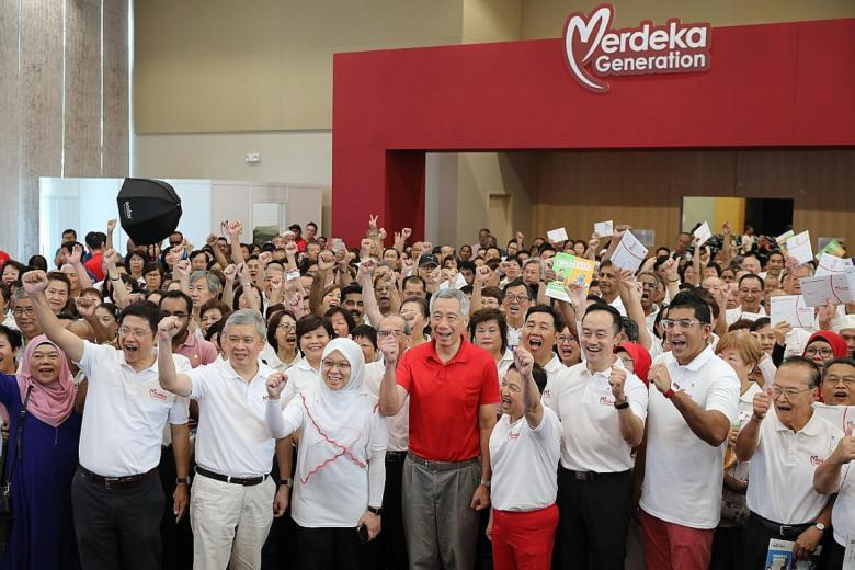Mr Lee Hsien Loong (in red) and advisers to Ang Mo Kio GRC grassroots organisations with 300 recipients of the Merdeka Generation Package.