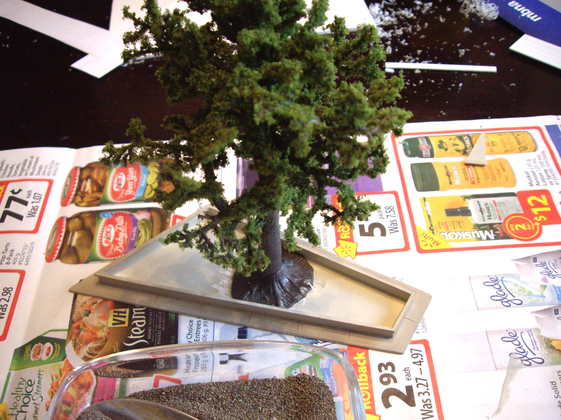 A deciduous tree armature with ground foam foliage being installed into a scratch built center median