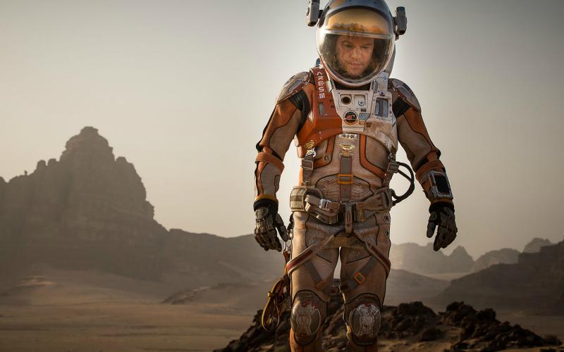 Na imagem: um astronauta caminha desolado por uma terra montanhosa e deserta, o planeta Marte. Sua roupa laranja e branca suja de terra. Ele olha para o chão.
