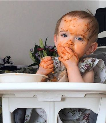 A baby eating spaghetti in a tomato based sauce with her hands