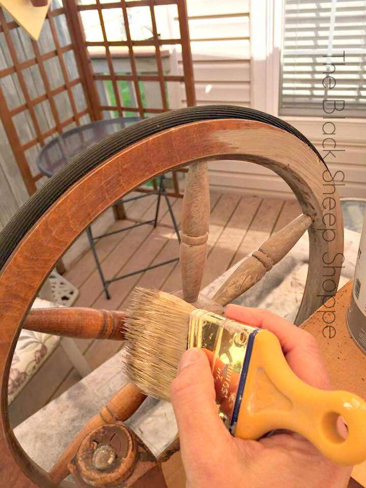 Painting the spindles on the wheels of the tea cart.