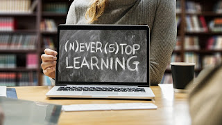 """Woman sitting behind laptop showing """"Never Stop Learning"""""""