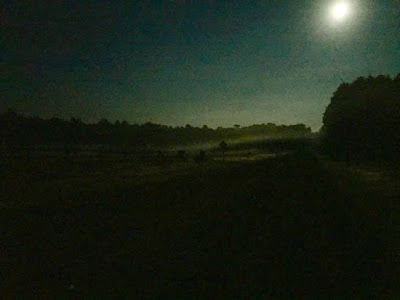 Full August moon on mist-covered fields