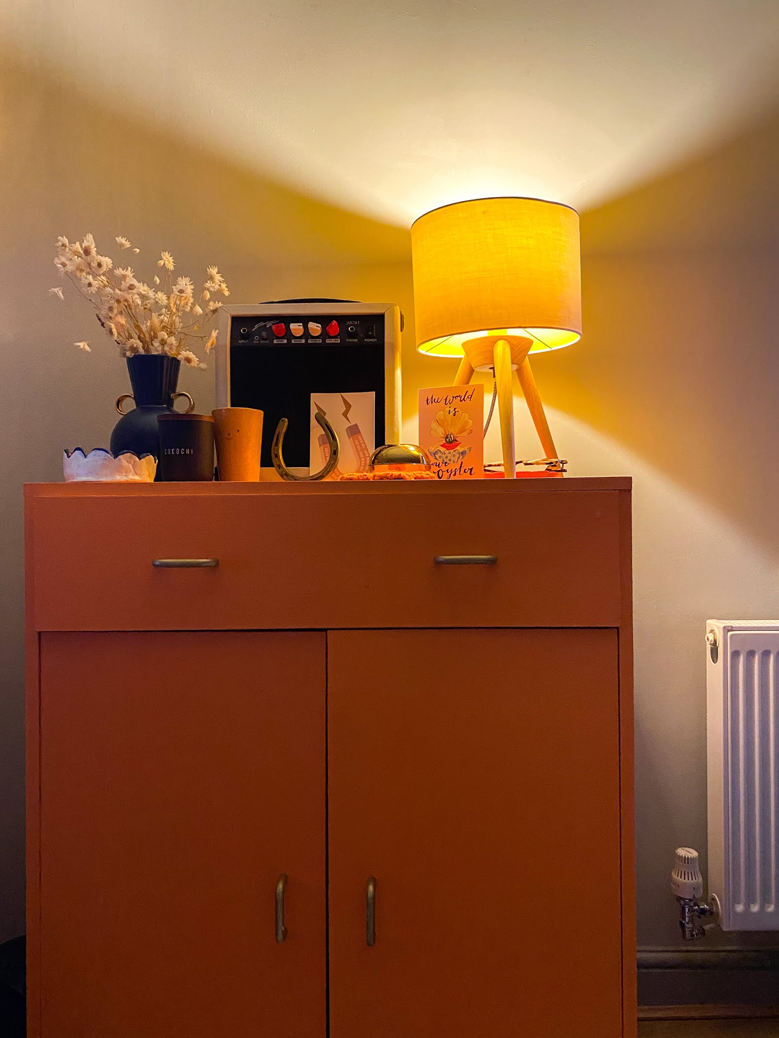 orange cupboard with soft light midcentury lamp styled with guitar amp and knick knacks