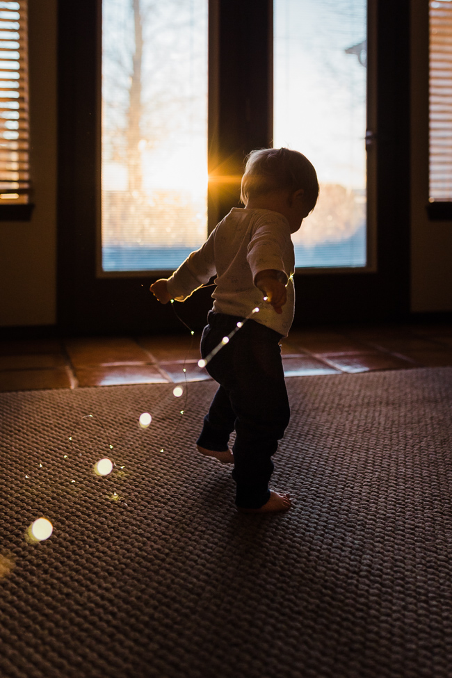 baby with twinkle lights and bokeh at sunset