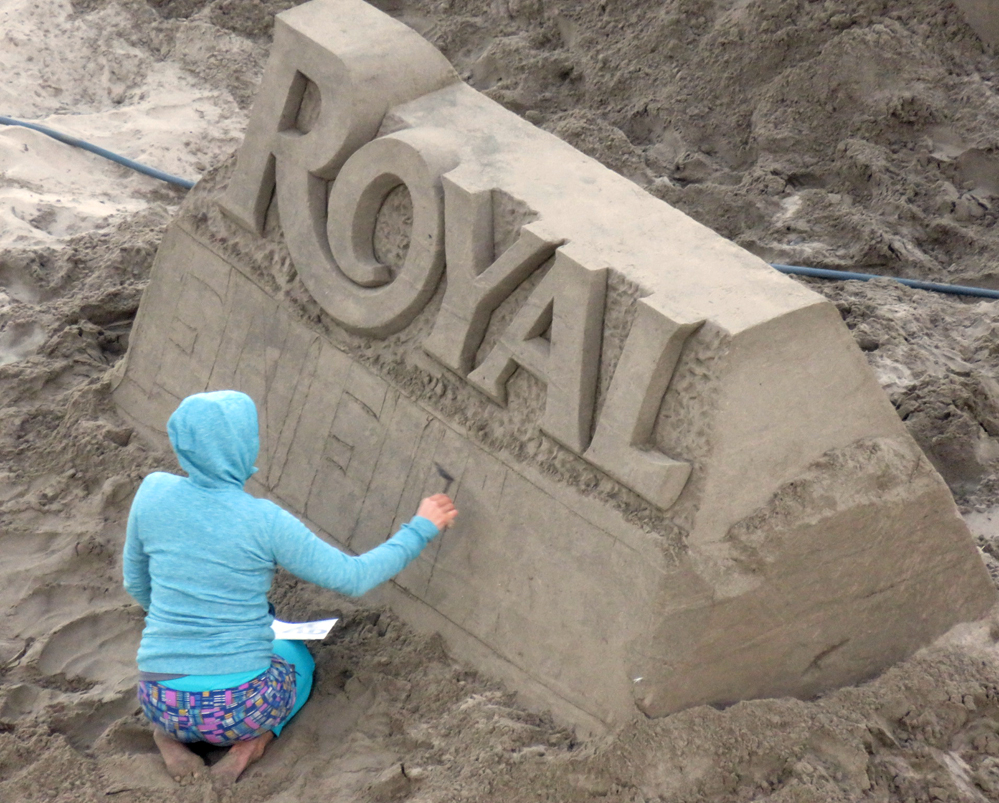 Woman sculpts the world Royal in sand.