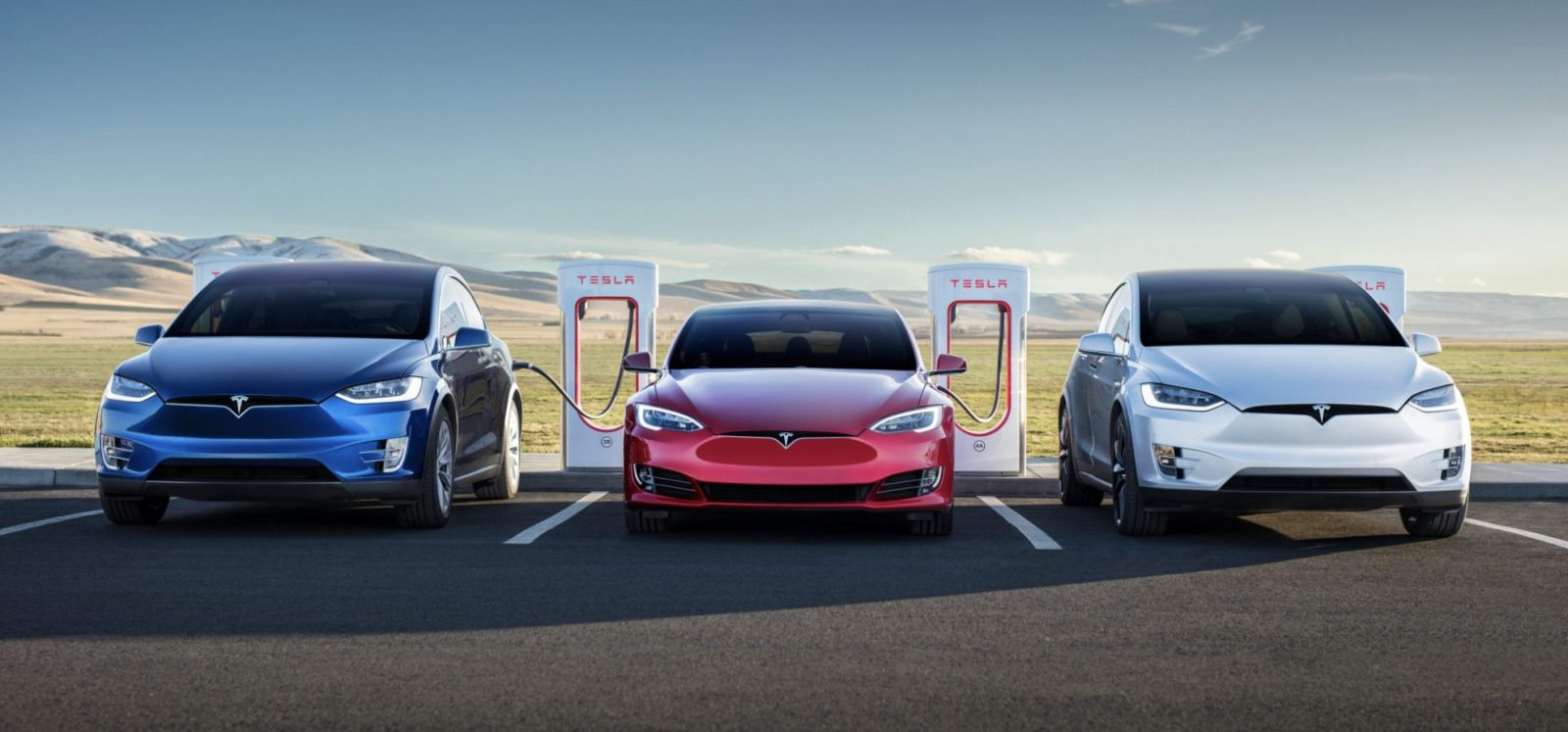 An array of Tesla model s and model x along with a supercharger