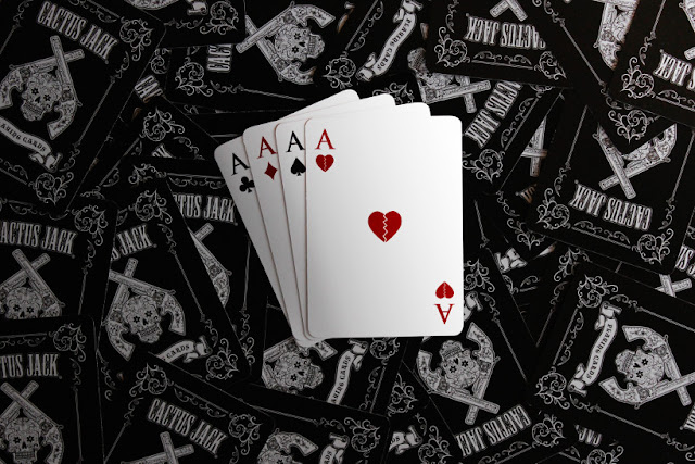 Four aces on a background of black playing card backs with a Wild West motif