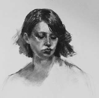 Female model looking down drawn in charcoal on pale blue paper