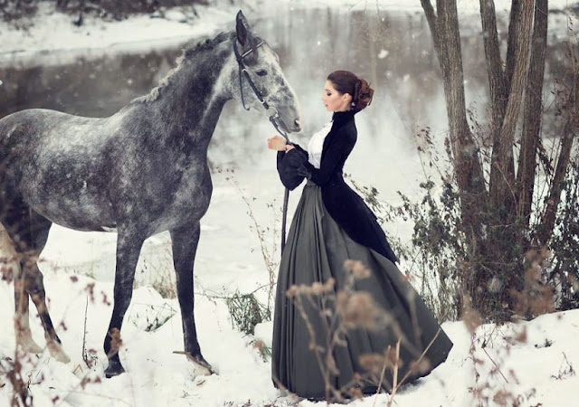 A woman wearing Victorian clothing in the snowy woods with her horse. Women's neo-victorian fashion.