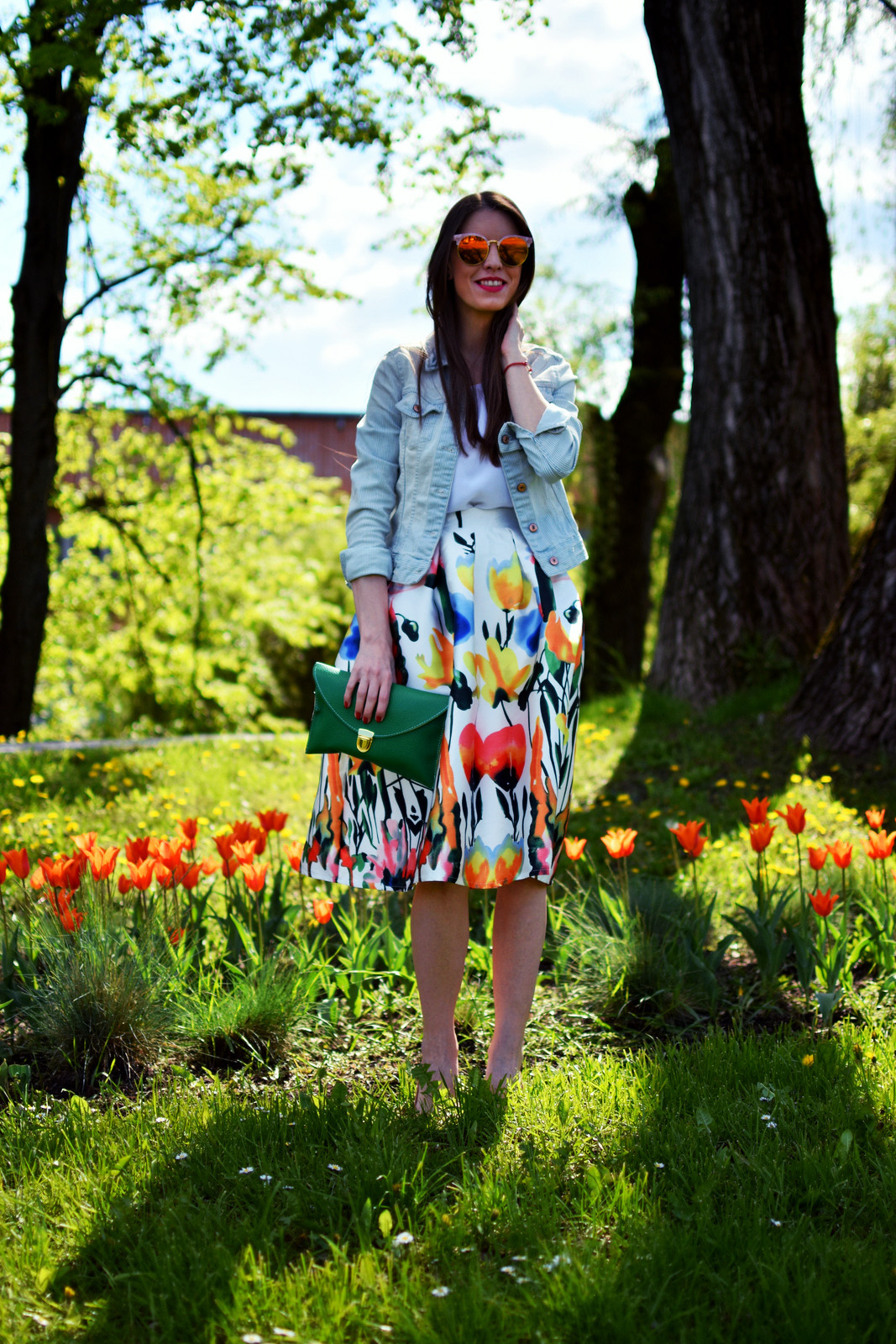 floral skirt with green clutch