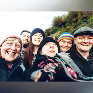 Family group portrait, faces squeezed in, laughing