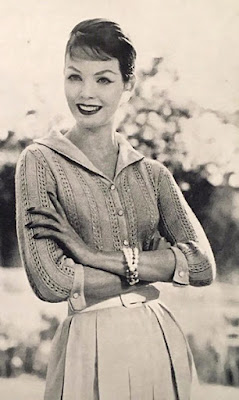 A 1950s photo of a woman in a knitted lacy blouse and pleated skirt