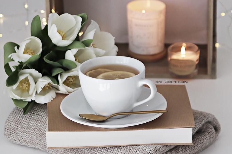 filiżanka herbaty, białe tulipany, świece i bokeh