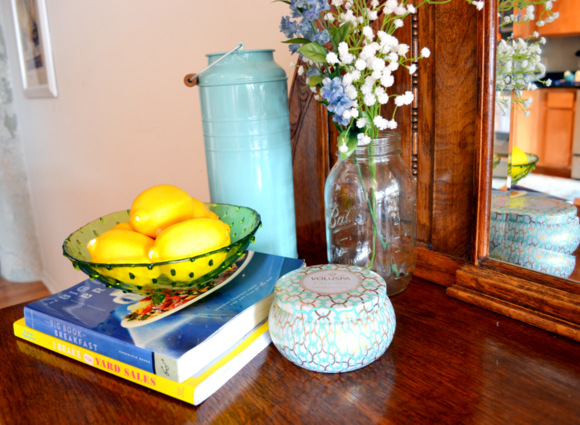 This counter top with books, a bowl of lemons, and fresh flowers is adorable.