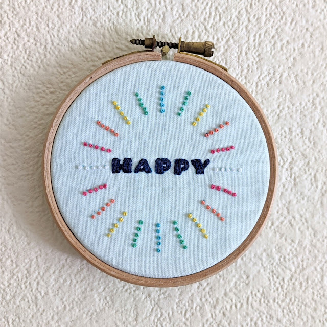 embroidery hoop with text Happy and rainbow french knots