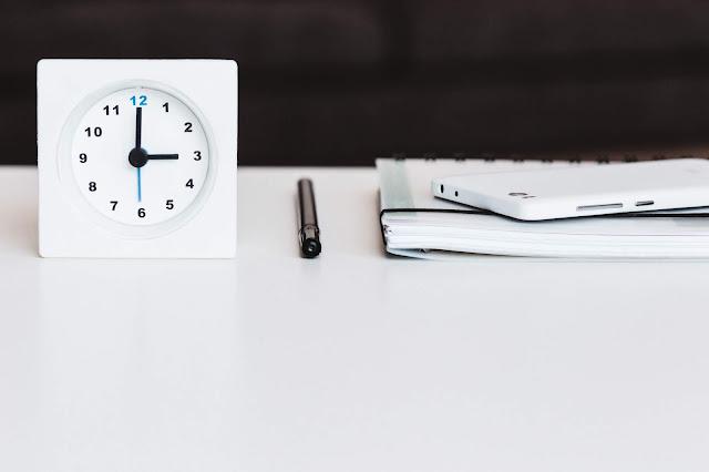 Relógio, caderno e canetas sobre uma mesa branca
