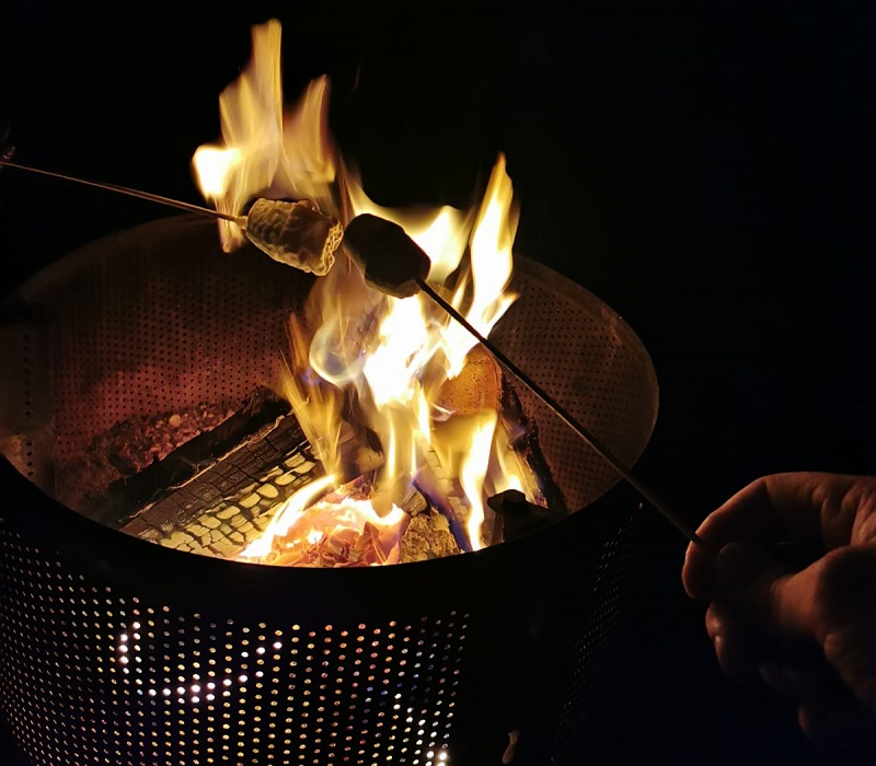 Toasting marshmallows on a camp fire in a recycled washing machine drum