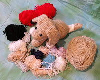 Above-view of crocheted dog surrounded by yarn scraps on three sides - in front and either side.
