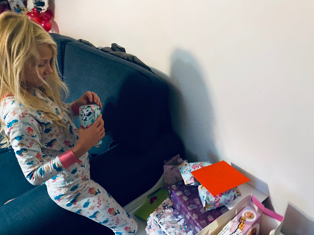 An 8 year old girl with long hair and mermaid pyjamas opening presents on her 8th birthday