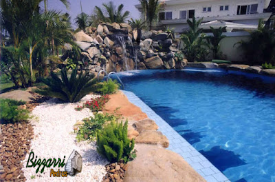 Cascata de pedra na piscina, tipo pedra moledo natural, com chapas de pedra na borda da piscina.