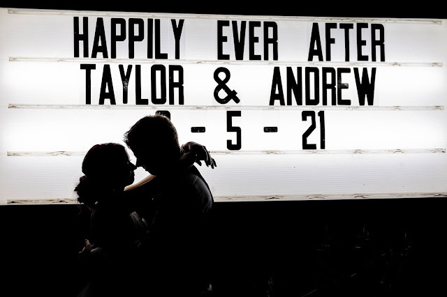 bride and groom silhouette against marquee board