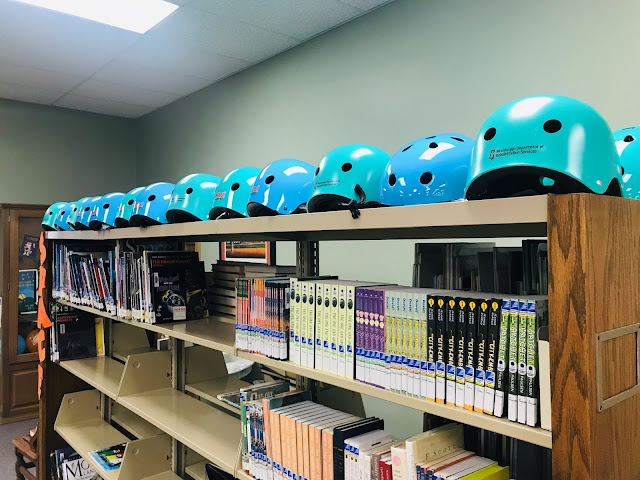 Bicycle helmets sit on top of library bookshelves. Books fill the bottom shelves.