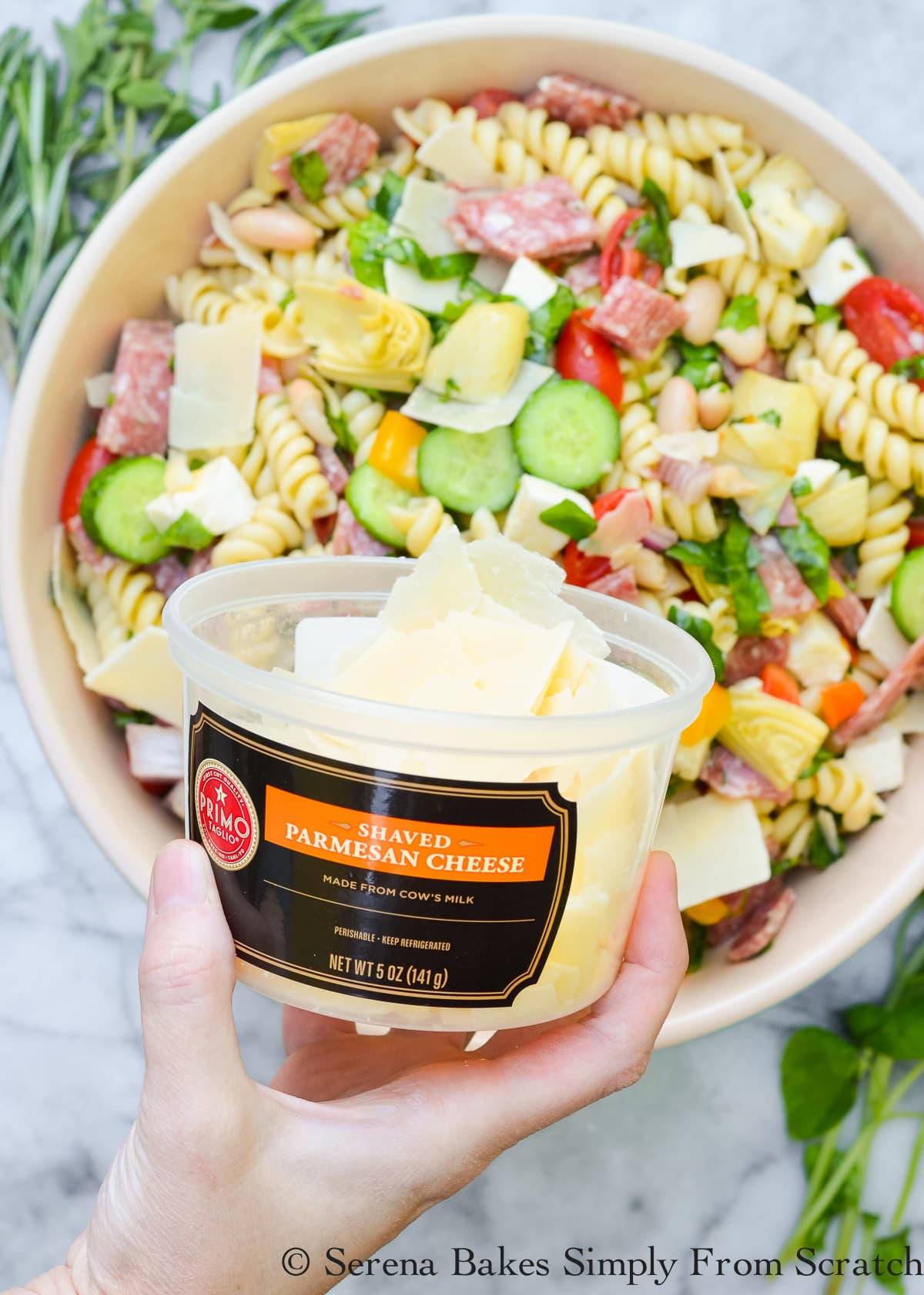 A plastic container of shaved Parmesan cheese being held by a hand holding it with a bowl of White Bean Salami Pasta Salad in the background.