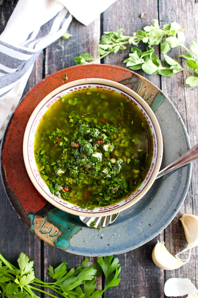 Top view of Chimichurri Sauce in a tan bowl on a ceramic multi-colored plate placed on a rustic wood background.