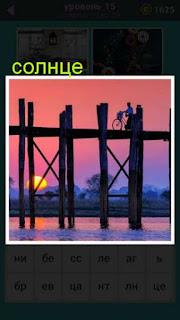 по мосту передвигается человек с велосипедом и пробивается солнце
