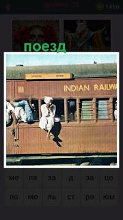 едет старинный поезд у которого на окне сидит человек свесив ноги