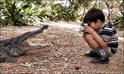 Niño tomando una foto con camara a la boca de un caiman