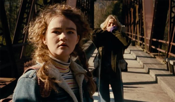 image of Regan (played by Millicent Simmonds) and Evelyn (played by Emily Blunt} standing on a bridge looking horrified in a scene from A Quiet Place