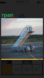 На взлетном поле двигается трап для самолета, по  которому сойдут пассажиры