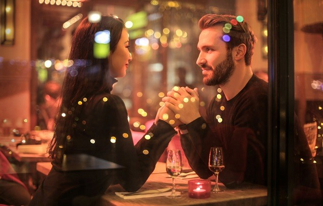 couple in a restaurant looking at each other holding hands