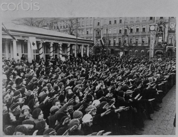 """18 ноября 1935 года. Рига. Люди с """"поднятой правой рукой под углом примерно в 45 градусов с распрямлённой ладонью"""" во время церемонии открытия памятника Свободы в день 17-летней годовщины независимости Латвии... И часы «Th. Riegert»"""