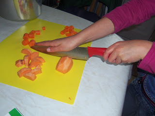 child chopping veg for soup